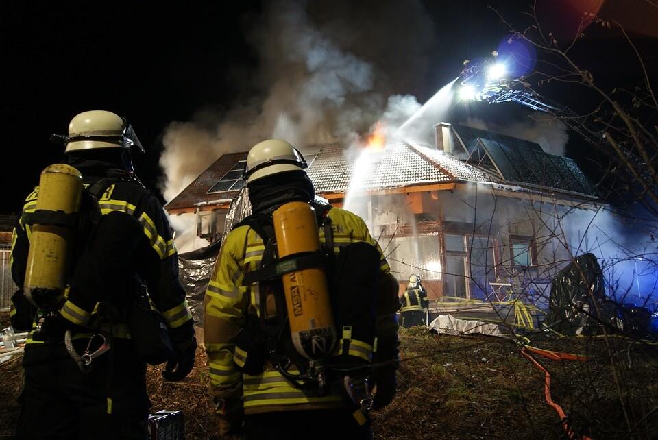 Ein brennendes Haus wird gelöscht von der Feuerwehr